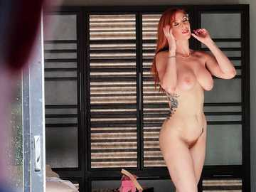Effective redhead babe Lauren Phillips poses naked in front of the guy and lets him suck her big breasts